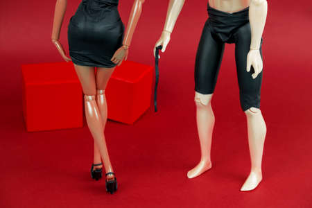man holding a whip  and a woman in a black leather dress on a red background, a creative still life with plastic dolls sex concept