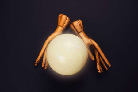 creative esoteric still life with a ball of predictions and two wooden female hands on  black background