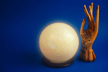 creative esoteric still life with a ball of predictions and wooden female hand on a vibrant blue background