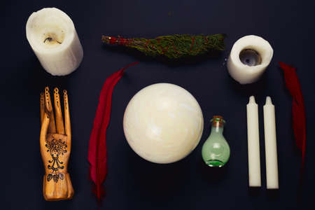 top view flat lay esoteric still life with candles,feather, potion, juniper ,crystal ball and wooden hand