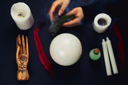 top view flat lay esoteric still life with candles,feather, potion,crystal ball, wooden hand and blurred female hands with smoking juniper