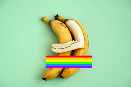 two bananas on a green background with LGBT flag, one banana hugs another with its peel