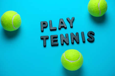 top view flat lay tennis balls and inscription play tennis  on a bright blue background