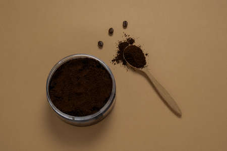 top view coffee scrub and wooden spoon with ground coffee on a beige background , homemade cosmetics concept