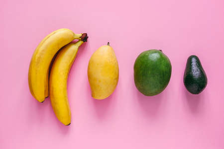top view layout of  fresh bananas,mangoes and avocado on a pastel pink background