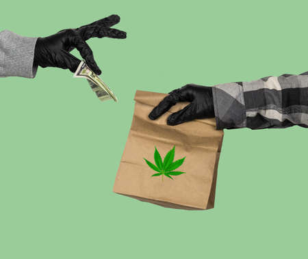 courier's hand in latex gloves holds a paper  bag with marijuana leaf  and female hand in latex gloves gives him