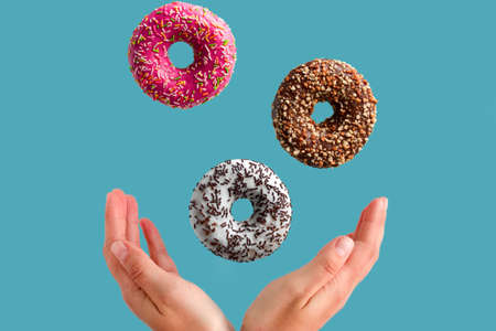 female hands and flying donuts on a blue background, junk food concept