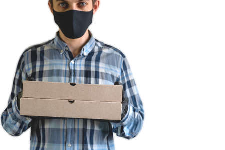 courier in a black mask and gloves with two cardboard boxes, close up of cardboard boxes against the background of a blurry man in a black mask