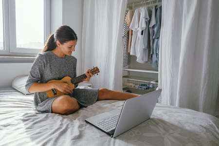 pretty young woman study to play ukulele guitar online at home with notebook sitting on the bed in the cozy bedroom