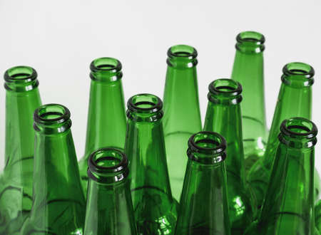 close up of green empty beer bottles on a white background