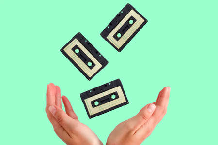 vintage audio tapes flying into female hands on a green background Banque d'images