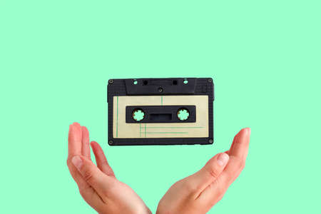 vintage audio tape flying into female hands on a green background Banque d'images