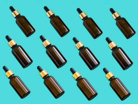 top view flat lay pattern cosmetic oil brown bottles on a blue background