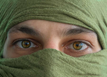 close up of the green eyes of a man whose face is covered with a blue bandage