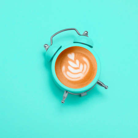 top view  coffee with latte art heart  in black alarm clock on a blue background