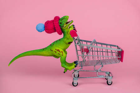 funny plastic toy dinosaur wearing tiny knitted hat and driving empty shopping trolley on a pink background ,shopping concept