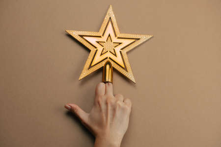 female hand showing middle finger decorated with golden star on a brown background