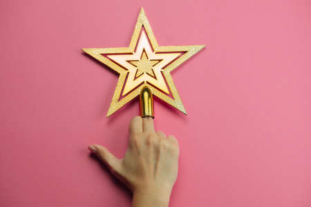 female hand showing middle finger decorated with golden star on a pink background Фото со стока