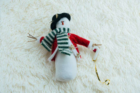 top view snowman toy on a white blanket