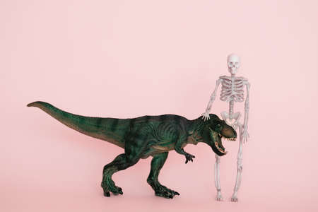 green dinosaur and human skeleton on a pink background selective focus