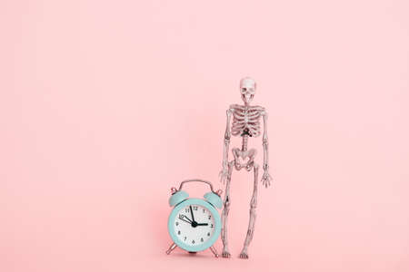 skeleton and alarm clock, deadline concept on a pink background Standard-Bild