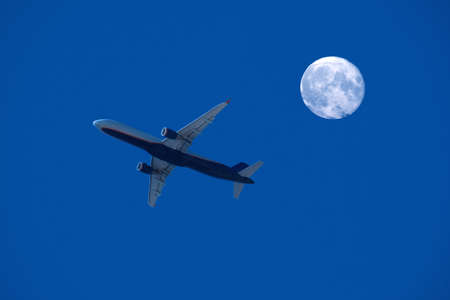 airplane flight against the full moon and night sky, aviation and travel concept 免版税图像