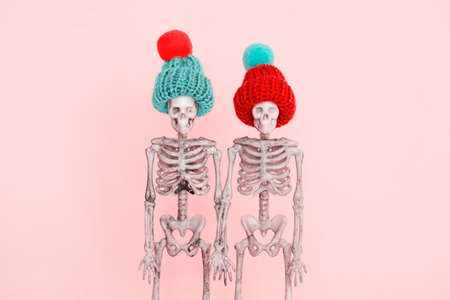 selective focus pair of skeletons wearing cute knitted hat on a pink background 版權商用圖片