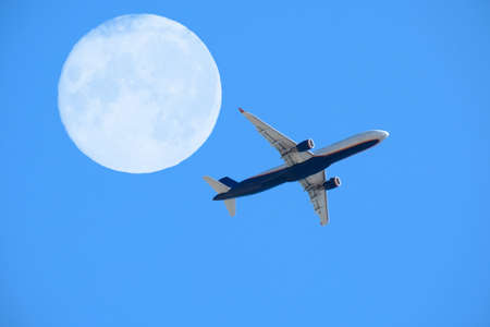 airplane flight against the full moon and blue sky, aviation and travel concept 免版税图像