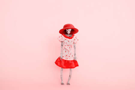 skeleton wearing pink dress and hat on a pink background selective focus