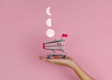 female hand holding shopping cart with moon flying into on a pink background, lunar calendar shopping concept