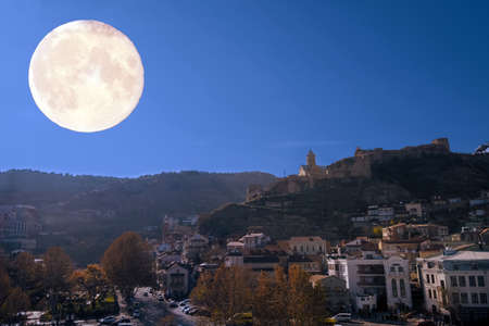 fantasy collage with night Tbilisi and full moon Banco de Imagens