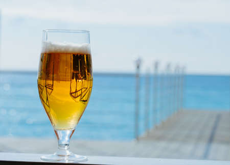 fresh cold glass of beer on a sea restaurant terrace in a sunny day, copy space blurred background