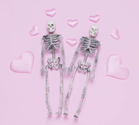 Top view skeleton couple and pink hearts pastel pink background. Minimal st. Valentines day card.