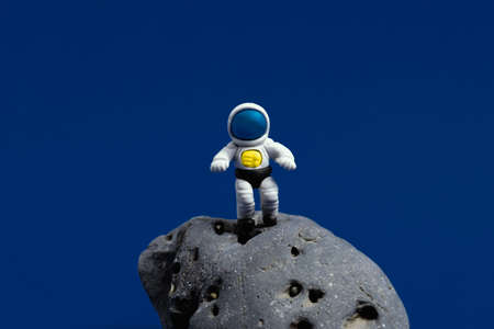 Cute miniature cosmonaut on a moon stone on a dark blue background. Minimal space day card.