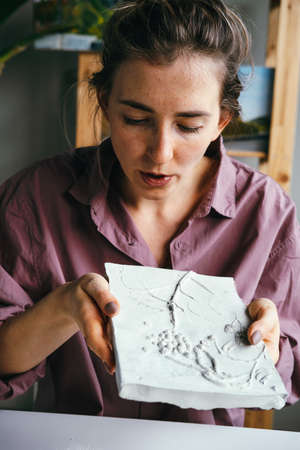 Young beautiful woman works with plaster relief. DIY and hobby concept.