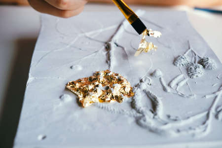 Close up plaster relief with golden foil. Handmade and art concept.