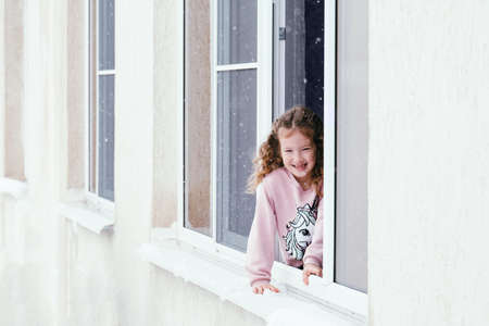Happy young girl positive portrait. Happy kid sitting on the windowsill and enjoying good winter weather.