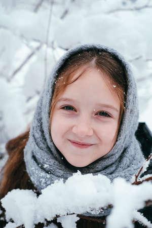 One pretty little girl wearing woolen gray scarf in a winter snowy forest cute portrait Banco de Imagens