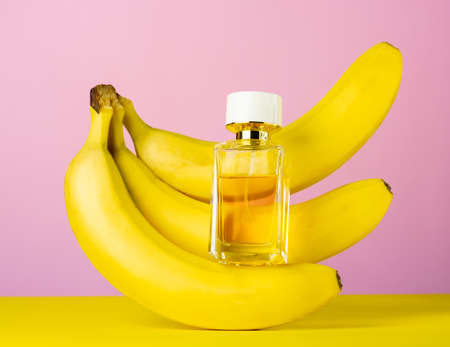 Perfume bottle and bananas pink yellow background, aromatherapy and beauty concept