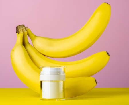 White mock up bottle and bananas pink yellow background, beauty care concept Banco de Imagens