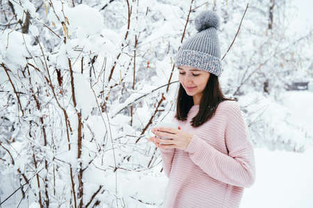 Cute young brunette woman wearing gray hat and pink sweater holding cup of warm drink outdoor in a winter park Banco de Imagens - 164980592