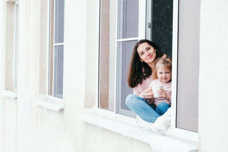 Cute portrait of mother and daughter sitting on a window sill at home with cup of hot drink. Banco de Imagens - 164980595
