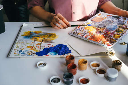 Close up working table of woman artist. Female hands with brush and paint