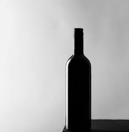 Black wine glass bottle on a gray background copy space selective focus