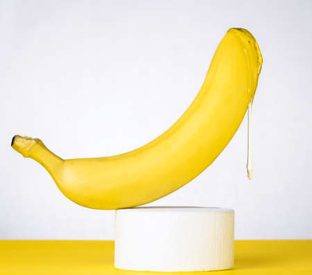 Banana with dripping honey on a white product stand