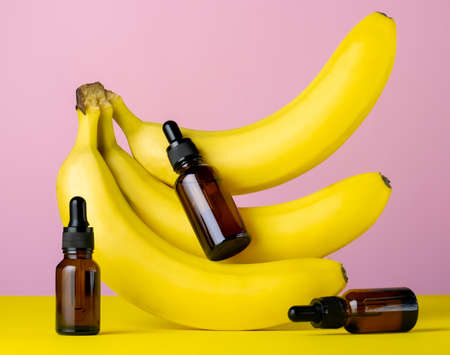 Moisturizing cosmetic oil brown glass bottles and bananas on a pink and yellow background, beauty care concept Banco de Imagens - 164970483