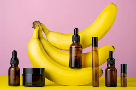 Moisturizing cosmetic oil brown glass bottles and bananas on a pink and yellow background, beauty care concept