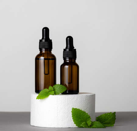 Brown glass bottles with herbal oil and green mint leaves on a product stage gray background Banco de Imagens