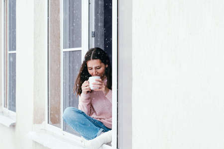 Beautiful brunette woman sitting on a window sill at home and drinking hot drink, cozy winter vacations portrait
