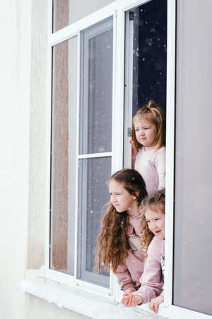 Three little girls lean out of the window and look at the falling snow Banco de Imagens